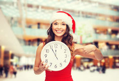 Smiling woman in santa helper hat with clock Stock Image