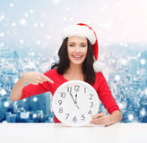 Smiling woman in santa helper hat with clock Royalty Free Stock Images
