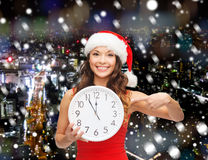 Smiling woman in santa helper hat with clock Stock Images