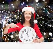 Smiling woman in santa helper hat with clock Royalty Free Stock Photography