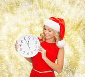 Smiling woman in santa helper hat with clock Stock Photos