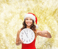 Smiling woman in santa helper hat with clock Stock Photo