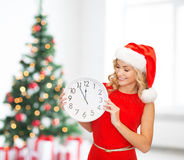 Smiling woman in santa helper hat with clock Royalty Free Stock Photos