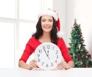 Smiling woman in santa helper hat with clock Stock Image