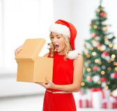 Smiling woman in santa helper hat with gift box. Christmas, x-mas, new year, winter, happiness concept - smiling woman in santa helper hat with magic gift box Stock Images