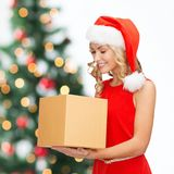 Smiling woman in santa helper hat with gift box. Christmas, x-mas, new year, winter, happiness concept - smiling woman in santa helper hat with gift box Royalty Free Stock Photo