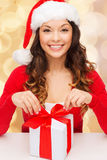 Smiling woman in santa helper hat with gift box. Christmas, holidays, celebration and people concept - smiling woman in santa helper hat with gift box over beige Stock Image