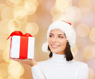 Smiling woman in santa helper hat with gift box. Christmas, winter, happiness, holidays and people concept - smiling woman in santa helper hat with gift box over Stock Photo