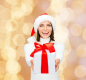 Smiling woman in santa helper hat with gift box. Christmas, winter, happiness, holidays and people concept - smiling woman in santa helper hat with gift box over Stock Images