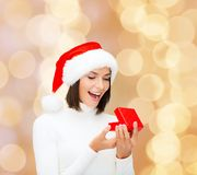 Smiling woman in santa helper hat with gift box. Christmas, winter, happiness, holidays and people concept - smiling woman in santa helper hat with gift box over Royalty Free Stock Image