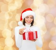 Smiling woman in santa helper hat with gift box. Christmas, winter, happiness, holidays and people concept - smiling woman in santa helper hat with gift box over Royalty Free Stock Photography