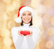 Smiling woman in santa helper hat with gift box. Christmas, winter, happiness, holidays and people concept - smiling woman in santa helper hat with small red Stock Image