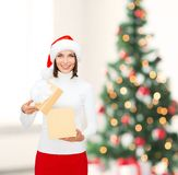 Smiling woman in santa helper hat with gift box Royalty Free Stock Photo
