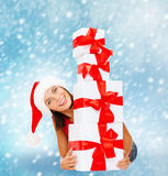 Smiling woman in santa helper hat with gift boxes Royalty Free Stock Photos