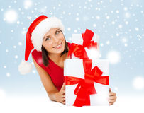 Smiling woman in santa helper hat with gift boxes Royalty Free Stock Images