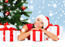 Smiling woman in santa helper hat with gift boxes Royalty Free Stock Image