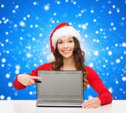Smiling woman in santa helper hat with laptop. Christmas, holidays, technology, advertisement and people concept - smiling woman in santa helper hat pointig Stock Photos