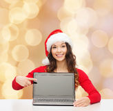 Smiling woman in santa helper hat with laptop. Christmas, holidays, technology, advertisement and people concept - smiling woman in santa helper hat pointig Royalty Free Stock Image