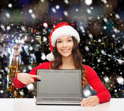 Smiling woman in santa helper hat with laptop. Christmas, holidays, technology, advertisement and people concept - smiling woman in santa helper hat pointig Royalty Free Stock Photo