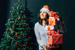 Smiling woman in santa helper hat with many gift boxes. Christmas, x-mas, winter, happiness concept - smiling woman in santa helper hat with many gift boxes Stock Photo