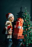 Smiling woman in santa helper hat with many gift boxes. Christmas, x-mas, winter, happiness concept - smiling woman in santa helper hat with many gift boxes Royalty Free Stock Photos