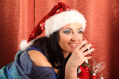 Smiling woman in santa helper hat over living room with christmas tree background Royalty Free Stock Images