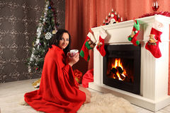 Smiling woman in santa helper hat over living room with christmas tree background Stock Photo