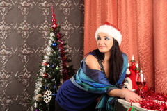 Smiling woman in santa helper hat over living room with christmas tree background Royalty Free Stock Photo