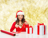 Smiling woman in santa helper hat packing gift box Stock Images