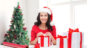 Smiling woman in santa helper hat packing gifts Stock Images