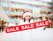 Smiling woman in santa helper hat with sale sign Royalty Free Stock Photo
