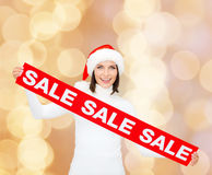 Smiling woman in santa helper hat with sale sign Stock Image