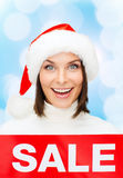 Smiling woman in santa helper hat with sale sign Royalty Free Stock Images