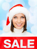 Smiling woman in santa helper hat with sale sign Royalty Free Stock Image