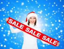 Smiling woman in santa helper hat with sale sign Stock Images