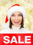 Smiling woman in santa helper hat with sale sign Stock Photography