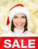 Smiling woman in santa helper hat with sale sign Stock Photo