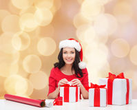Smiling woman in santa helper hats packing gifts Stock Photos