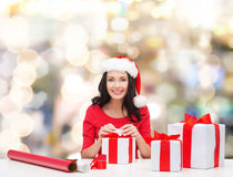 Smiling woman in santa helper hats packing gifts Stock Photography