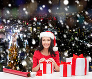 Smiling woman in santa helper hats packing gifts Stock Images
