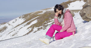 Smiling woman sat on snowy mountain summit Royalty Free Stock Images