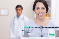 Smiling woman on the scale Stock Photography
