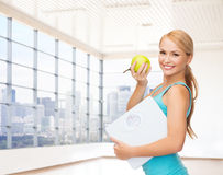 Smiling woman with scale and green apple in gym Royalty Free Stock Images