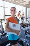 Smiling woman with scales and towel in gym Stock Photos