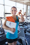 Smiling woman with scales and towel in gym Royalty Free Stock Photos