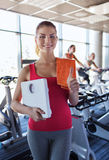 Smiling woman with scales and towel in gym Royalty Free Stock Photo