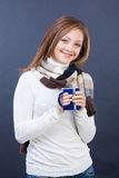 Smiling woman in scarf with cup of tea. Studio shot of beautiful young smiling woman in stripped scarf with cup of hot tea Stock Photos