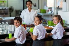 Smiling woman with schoolchildren in canteen. Portrait of smiling women with schoolchildren in canteen royalty free stock photo