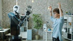 Smiling woman controlling robot testing response, machine copying movements