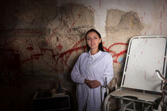 Smiling woman scientist in front of a blood splattered wall. Halloween concept Stock Photography